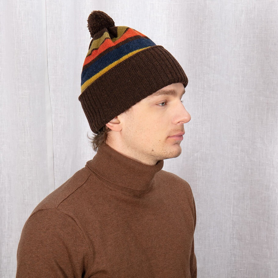Flerfärgad brun mössa med uppvikt kant och liten boll