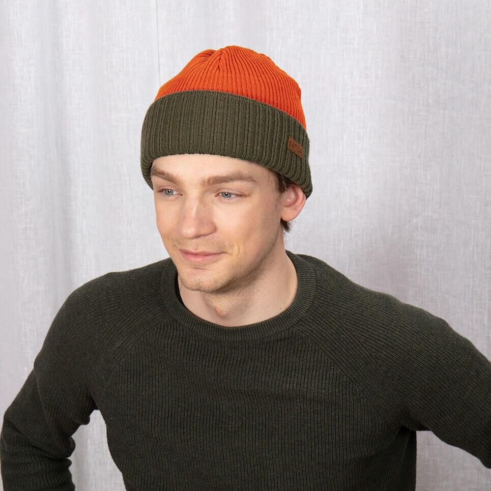 Mörkgrön och orange mössa med uppvikt kant