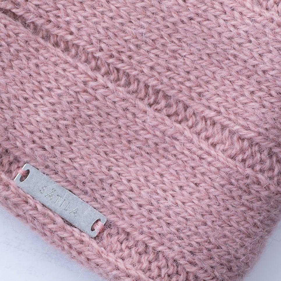 Dovt rosa pannband, närbild på stickningen och Sätilas metallabel