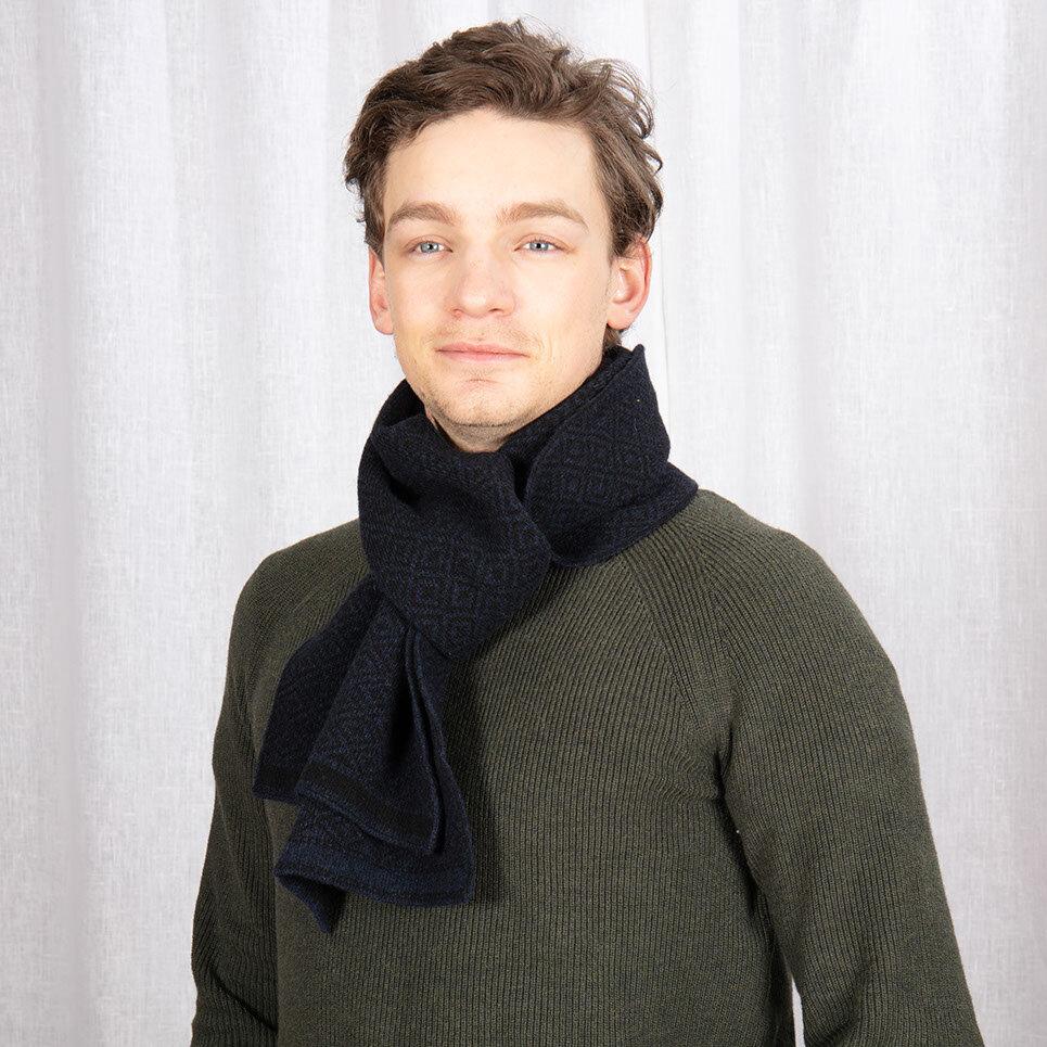 Stickad halsduk i svart och mörkblått med ett diskret mönster