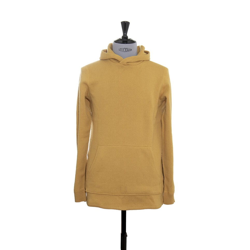 En gul stickad hoodie för både dam och herr med en stor magficka och en stor luva