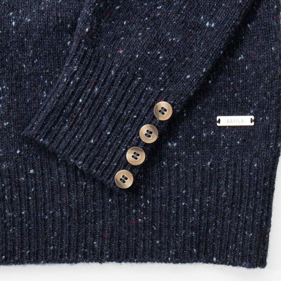 Högalid dress är en mörkblå klänning i melerat garn med fina knappar som detalj vid ärmslut