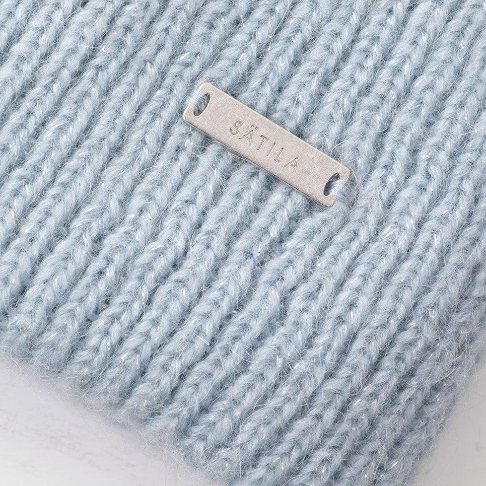 Närbild på ljusblå stickad mössa med Sätilas metall-label