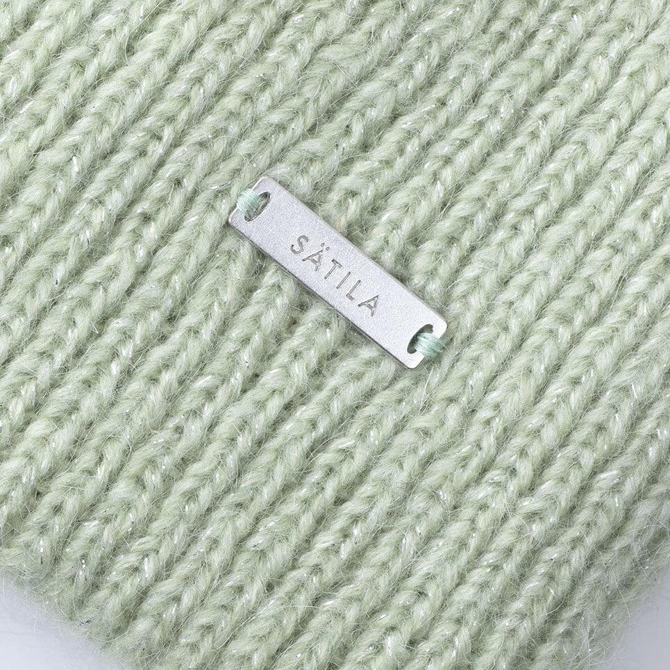 Närbild på ljusgrön stickad mössa med Sätilas metall-label