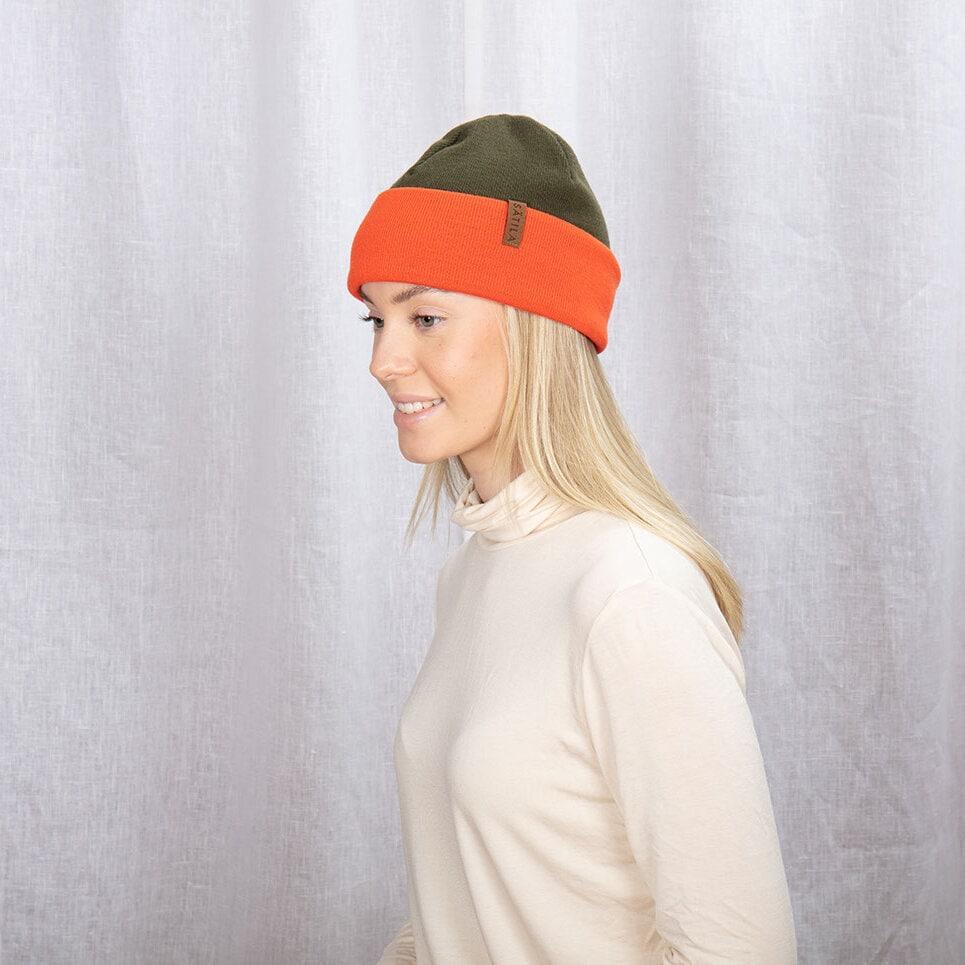 Grön och orange vändbar mössa med uppvikt kant och Sätilas mockalabel
