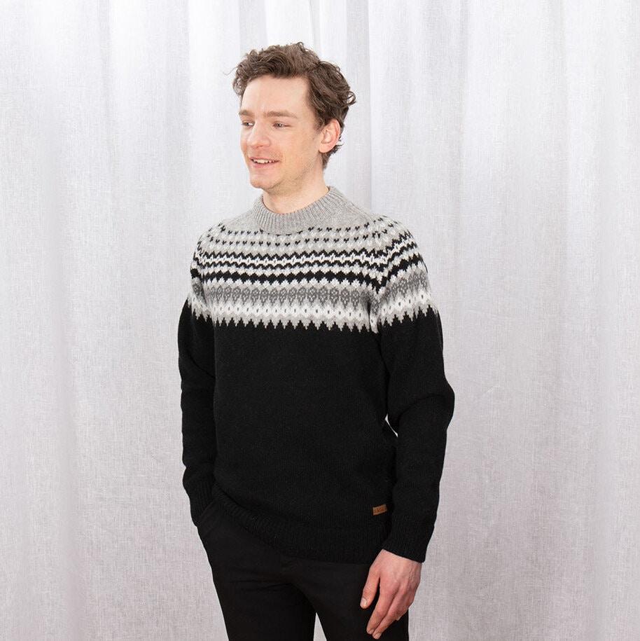 Stickad tröja i svart med klassiskt mönster upptill i grått, vitt och svart