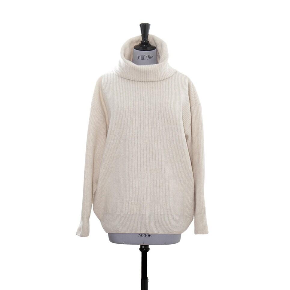 En beige, varm och rejäl stickad tröja för dam med en stor och bekväm polokrage